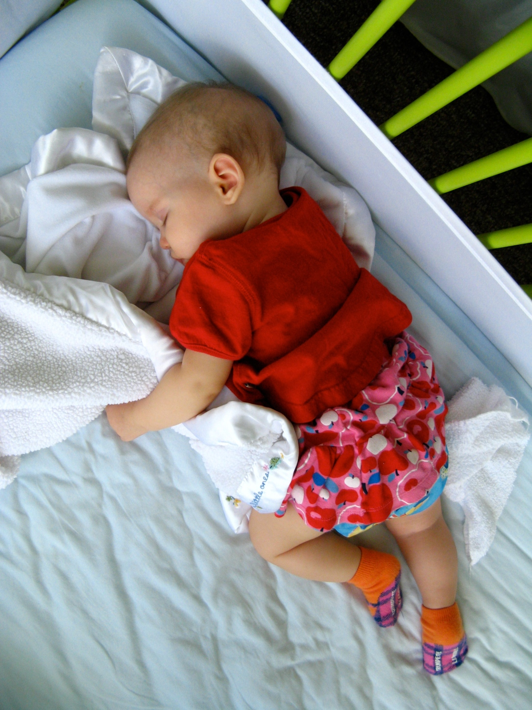 Six month old baby Aveline sleeping peacefully in crib, holding baby blanket, wearing Trumpette socks