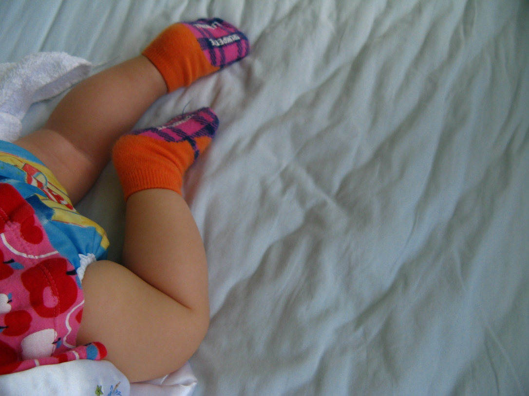 Baby sleeping in crib wearing Bummi cloth diaper cover and Trumpette socks