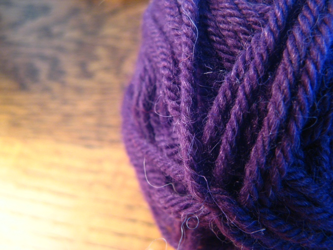 purple yarn with wood grain table in background