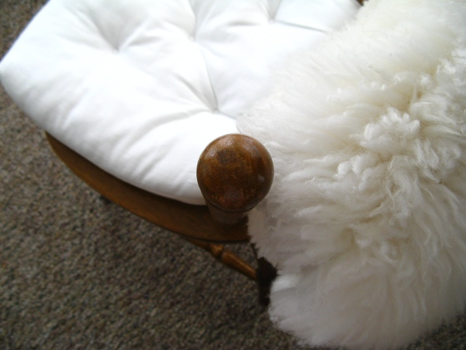 wooden kitchen chair with white IKEA RITVA cushion and IKEA RENS sheepskin