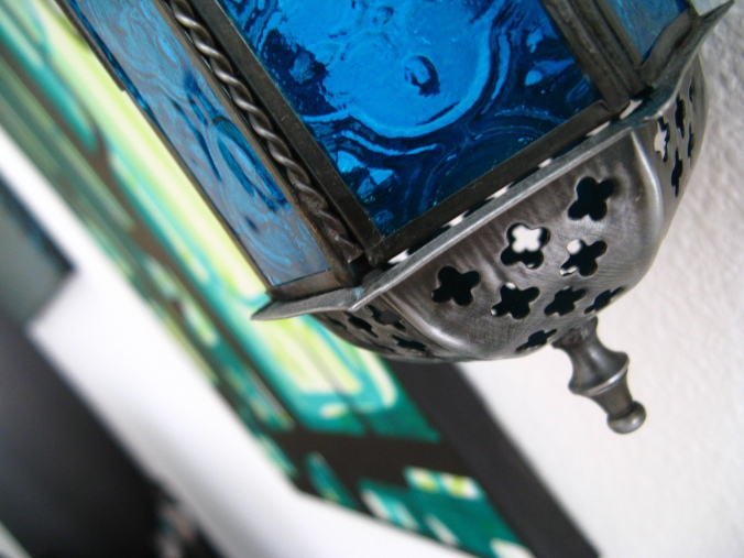 blue Moroccan lantern with green and black canvas in background