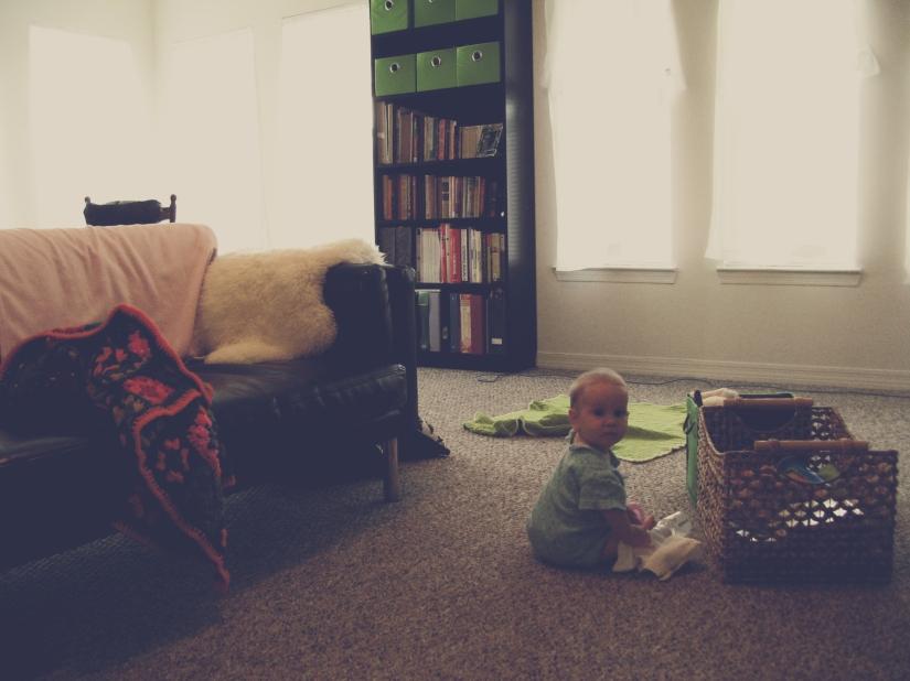 Aveline sitting near toy basket in morning light in living room