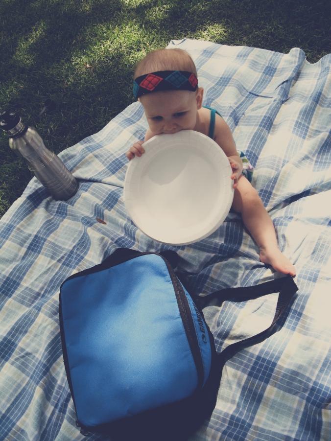 Baby chewing on paper plate waiting for picnic - Baby sitting on plaid picnic blanket