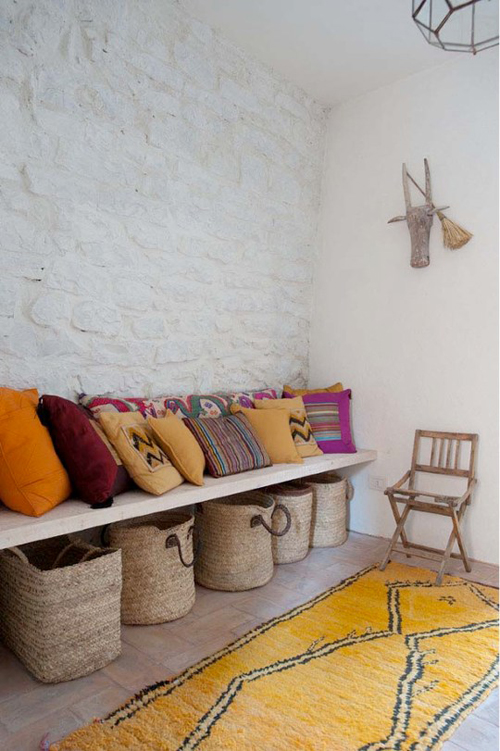 Italian Cottage via Cote Maison and Style Files - Yellow Rug, Stone Walls, Pillows, and Natural Baskets