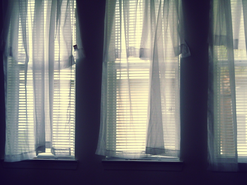 Three windows with white sheer curtains hanging crooked and uneven