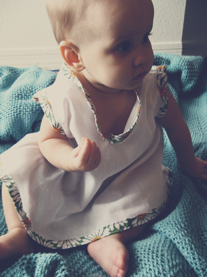 Aveline in a handmade white cotton baby dress with daisy trim