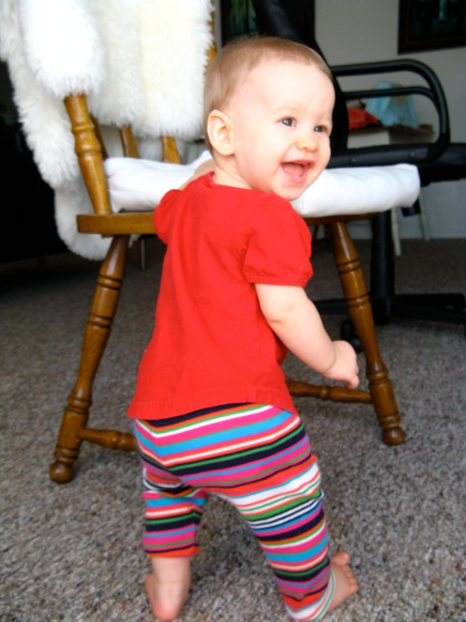 Happy baby wearing striped leggings standing up next to wooden chair with IKEA Rens sheepskin and chair cushion