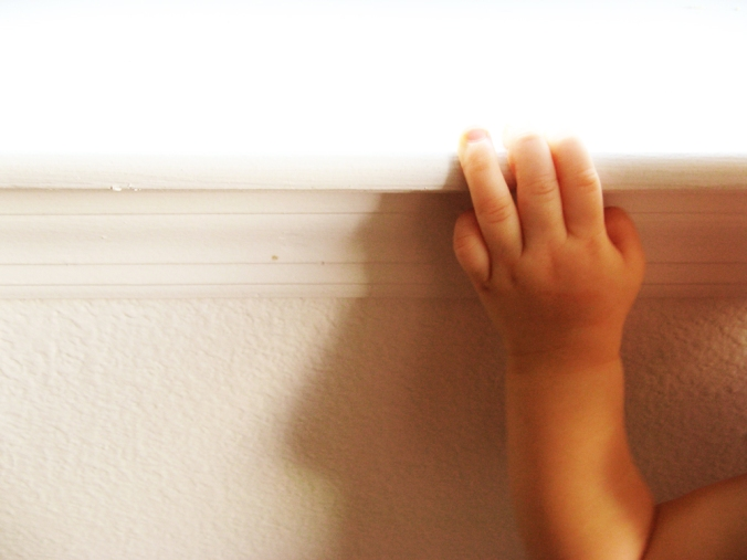 Baby hand on white windowsill
