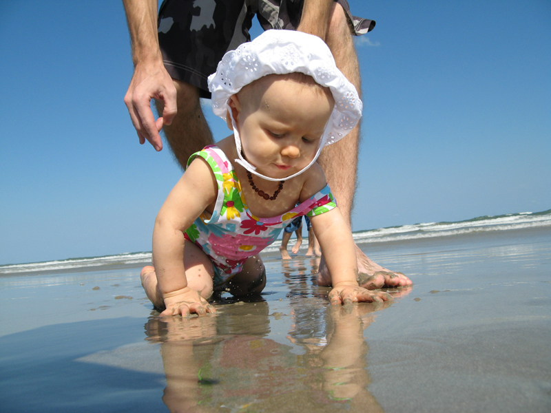 Aveline crawling near the ocean with Josiah right behind her