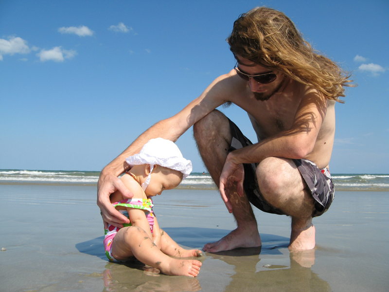 Josiah with Aveline as she sits in the wet sand at the ocean's edge
