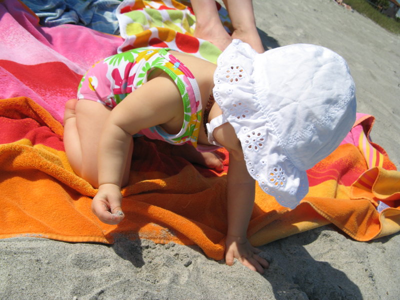 Baby on beach towel in eyelet lace sunhat holding handful of sand