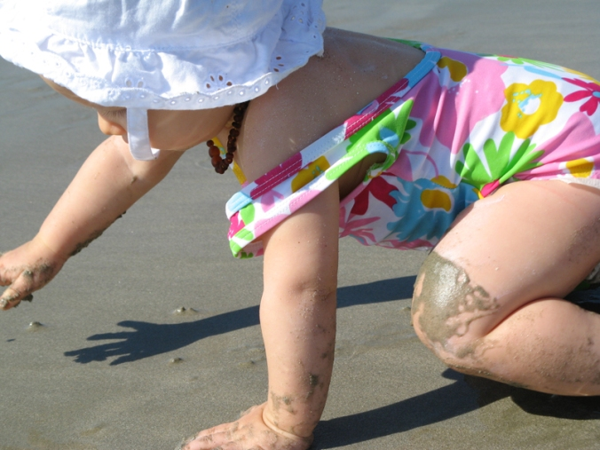 Baby in floral swimsuit, sunhat, and raw amber necklace crawling in the sand