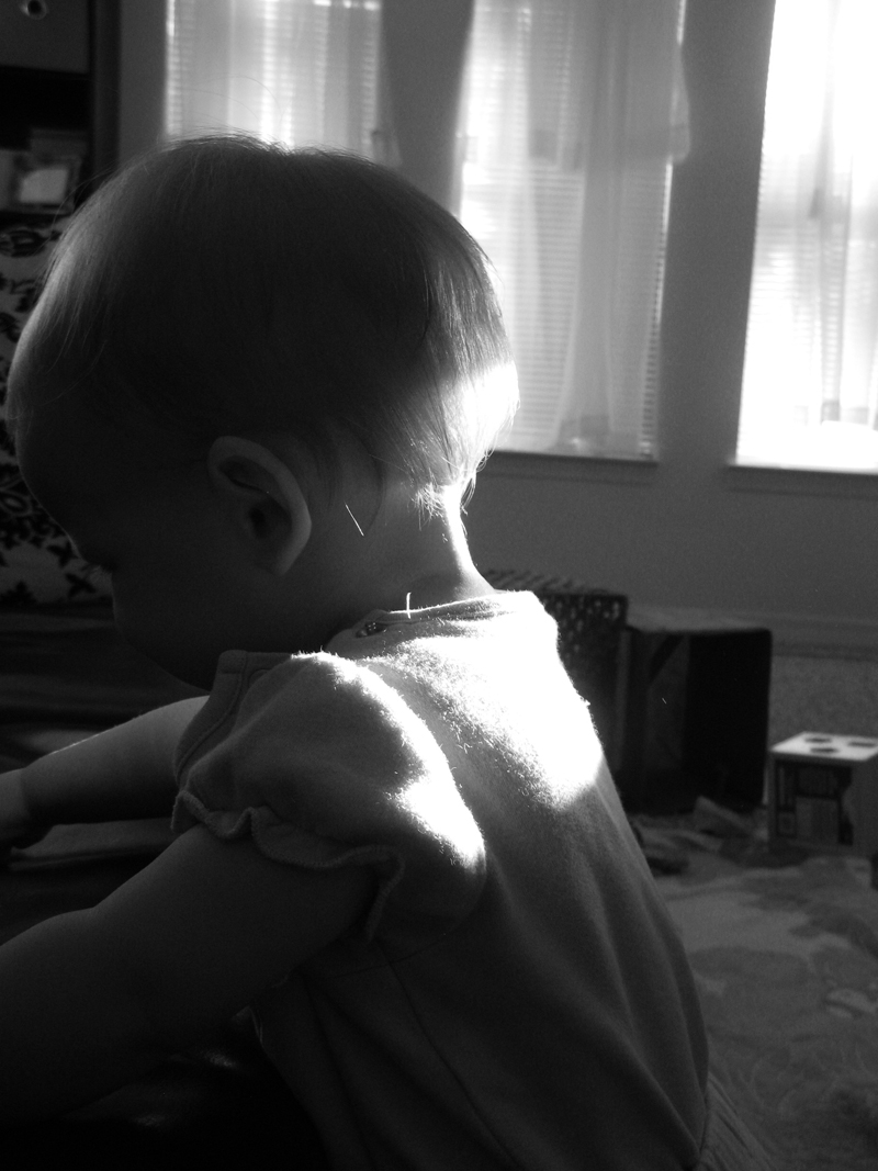 Black and white photo of morning light shining on back of baby's head