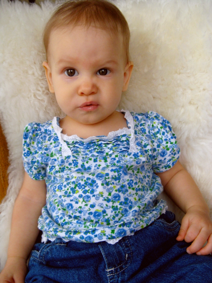 Baby in jeans and The Childrens Place calico shirt, sitting on sheepskin