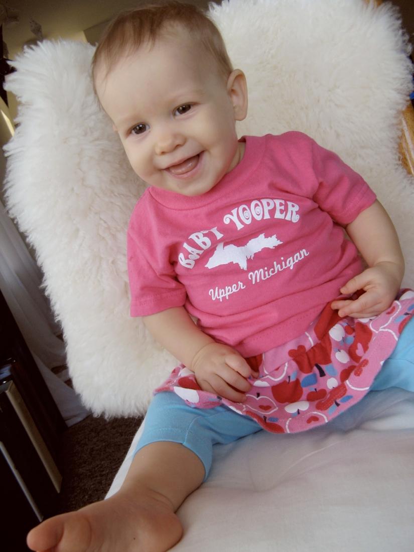 Aveline in Baby Yooper tshirt, leggings and skirt, on chair