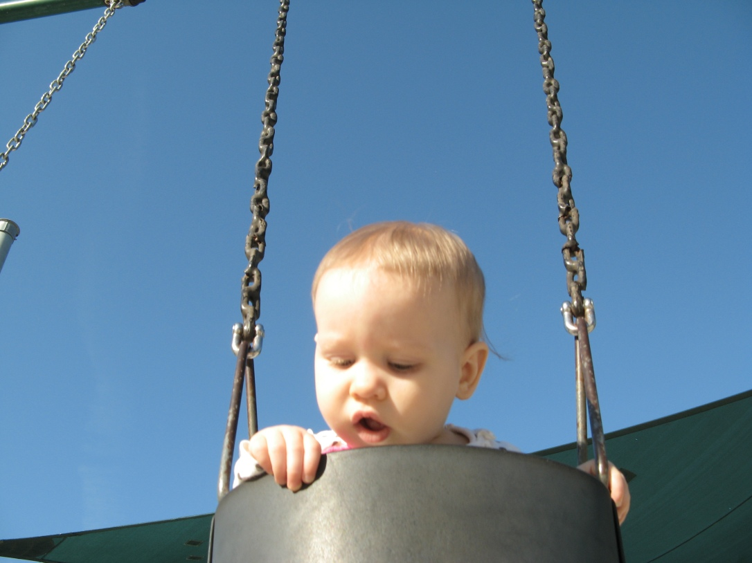 Aveline peeking over the edge of the swings