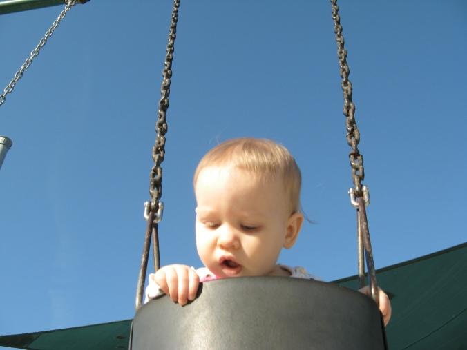 Aveline peeking over the edge of the swings