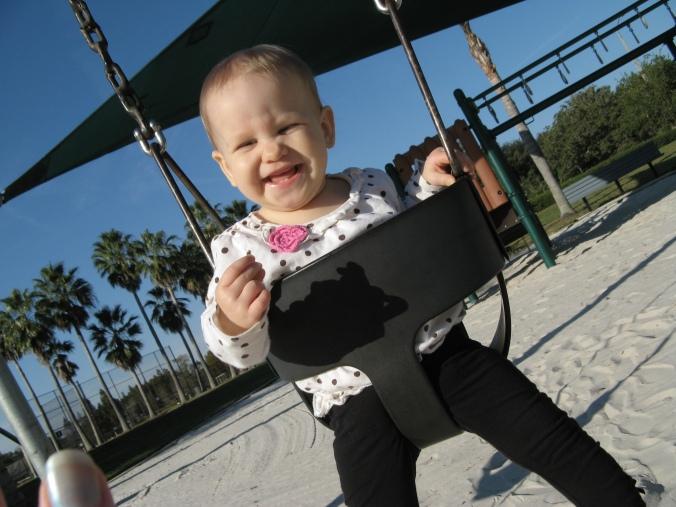 Aveline smiling on the playground swing