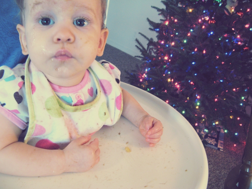Baby in highchair next to Christmas tree