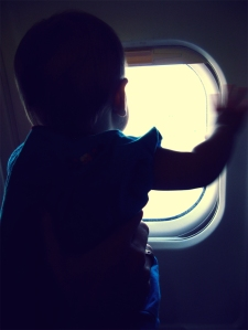 Silhouette of baby in window of airplane