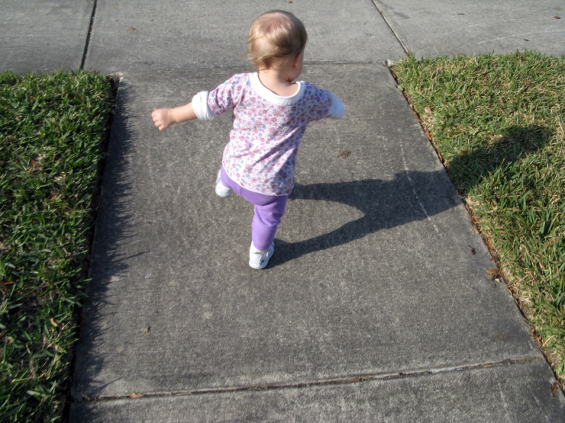 Toddler Aveline running down the sidewalk