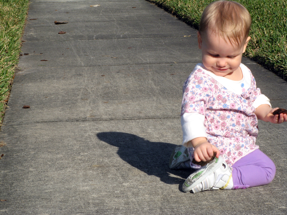 Toddler Aveline kneeling on sidewalk holding bark pieces