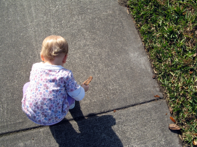 Toddler Aveline stooping down to pick up bark off the sidewalk