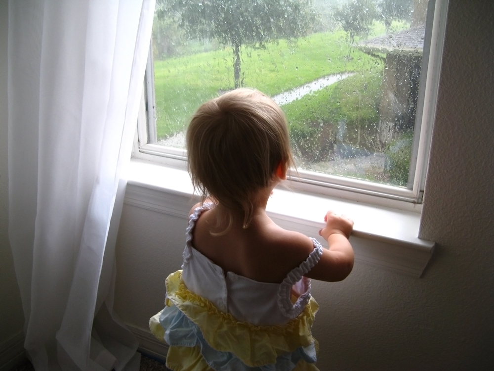 Toddler standing in front of rainy window