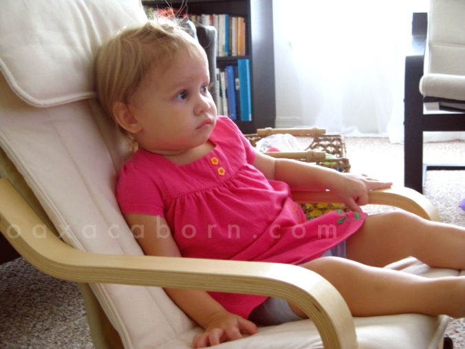 Toddler in fluorescent pink dress sitting in a mini IKEA Poang chair
