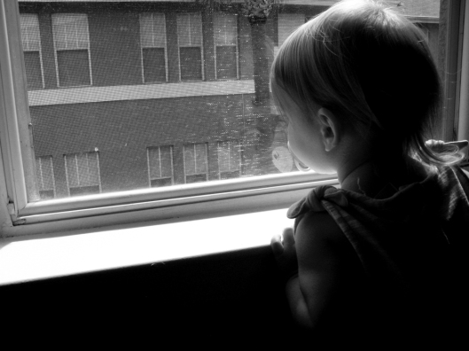 Toddler looking out of apartment window - Black and white photo via Oaxacaborn dot com