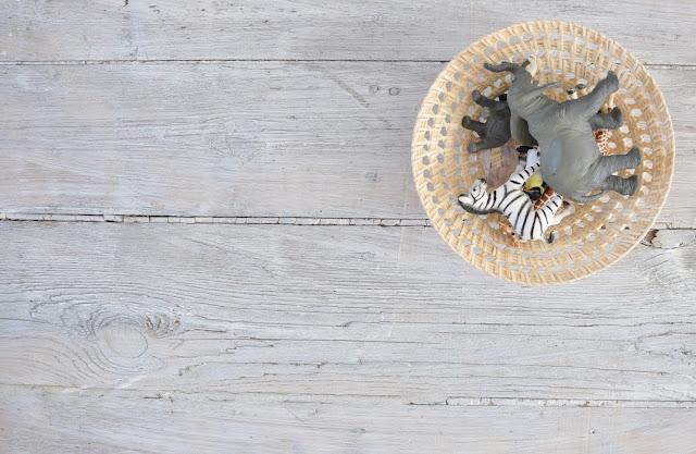 Le Dans La - Plastic Animals in Basket on Wooden Floor
