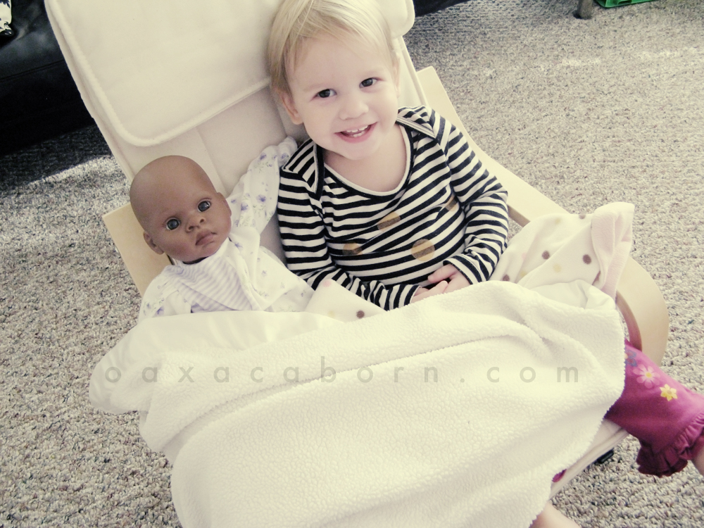 Aveline with doll and blanket in small Ikea Poang chair, wearing Misha Lulu shirt, photo via Oaxacaborn dot com
