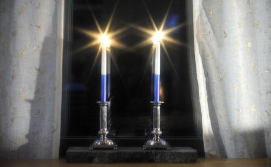 Two candles for itsenäisyyspäivä on window sill - photo via Studio55.fi