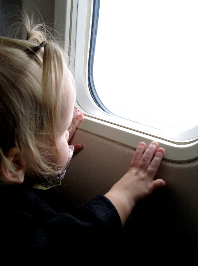 Toddler looking out airplane window - via the Oaxacaborn blog - photo by Gina Munsey