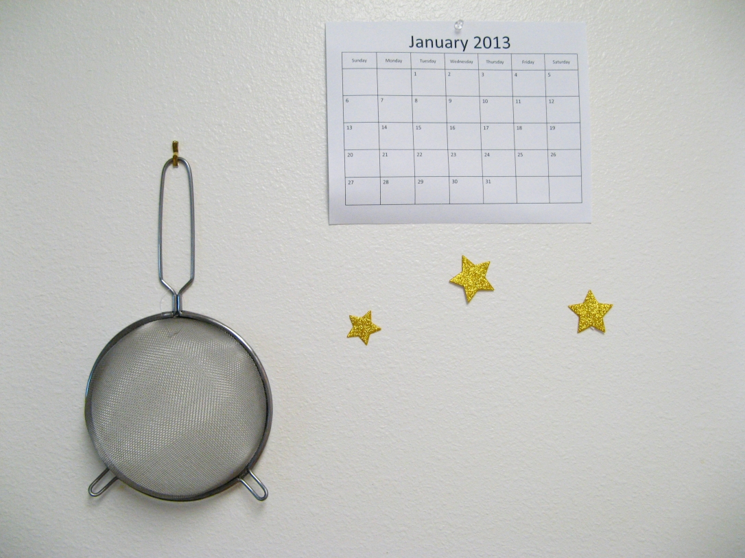 Colander, calendar, and stars on white kitchen wall - photo via Oaxaacborn dot com