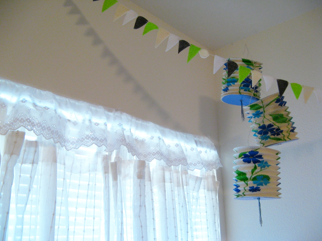 Curtains, bunting, and lanterns in the corner of Aveline's room