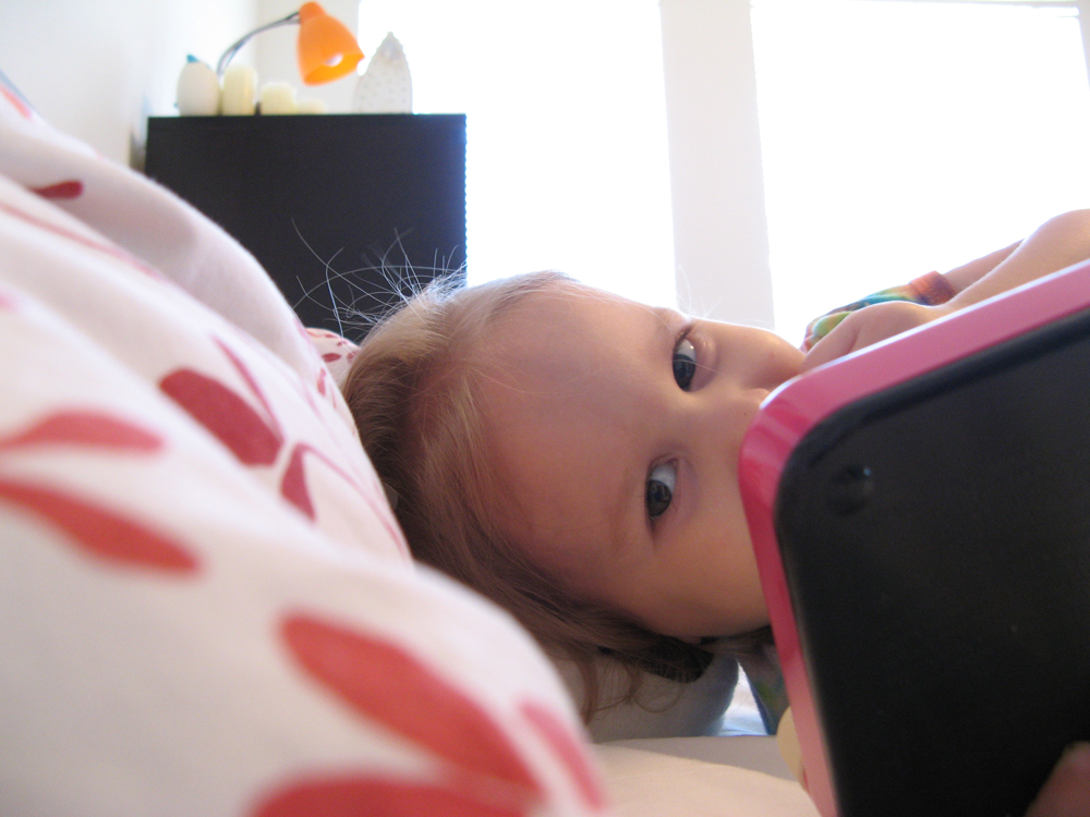 February 2013 - Aveline eating Ritz and playing Etch-a-Sketch in our bed
