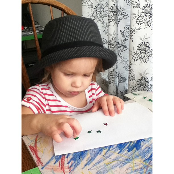 Fedora-wearing toddler making art projects