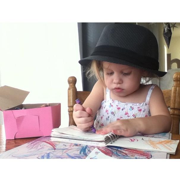 Fedora-wearing toddler coloring