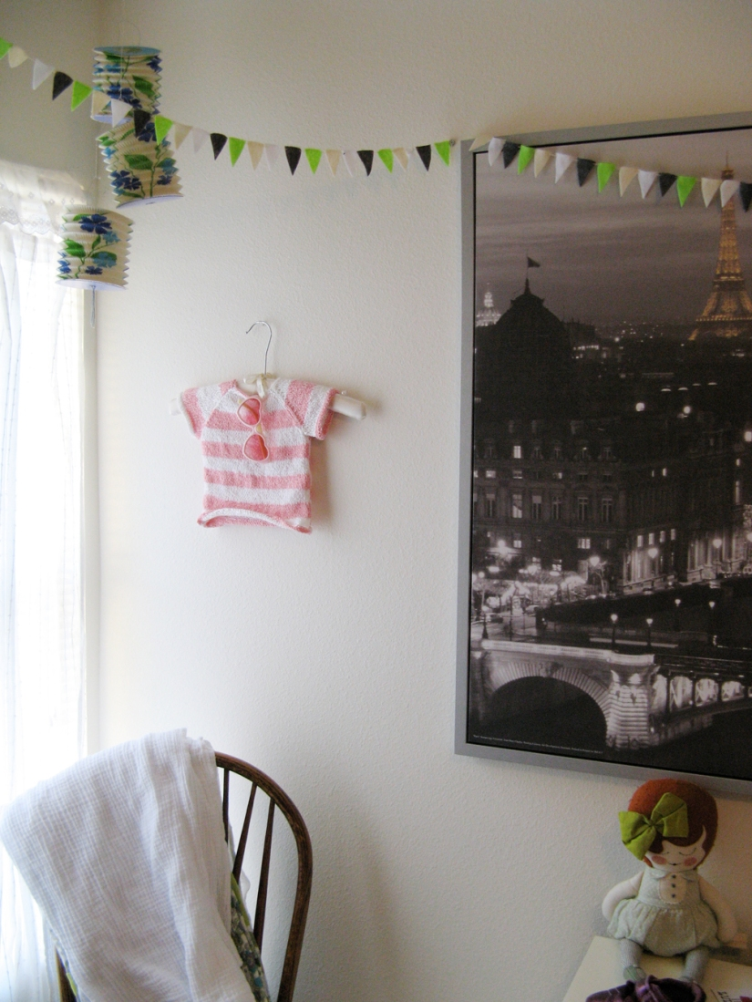 Aveline's room tour via Oaxacaborn - Huge framed canvas of Paris, bunting, paper lanterns, blankets over chair and doll