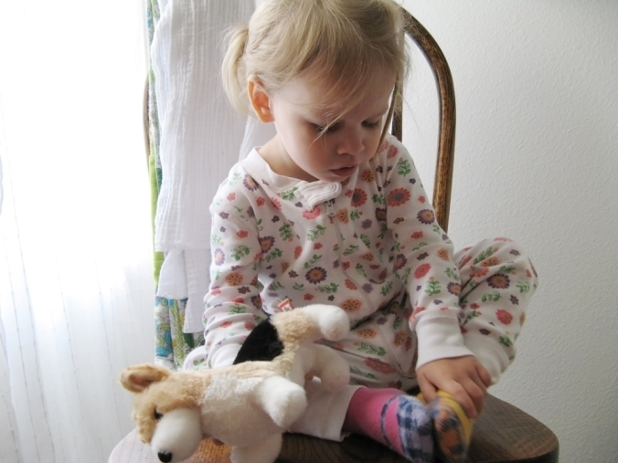 Toddler in Hanna Andersson pajamas with stuffed animal dog