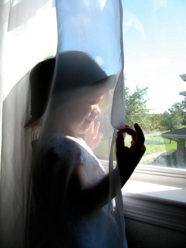 Aveline holding curtain near window via Oaxacaborn