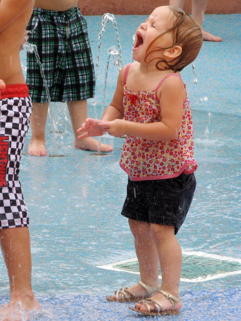 Toddler happily yelling at splashpad via Oaxacaborn