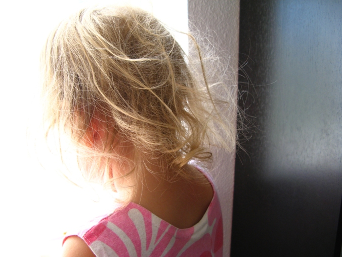 August 2013 - Aveline's tangled hair looking out window in morning light