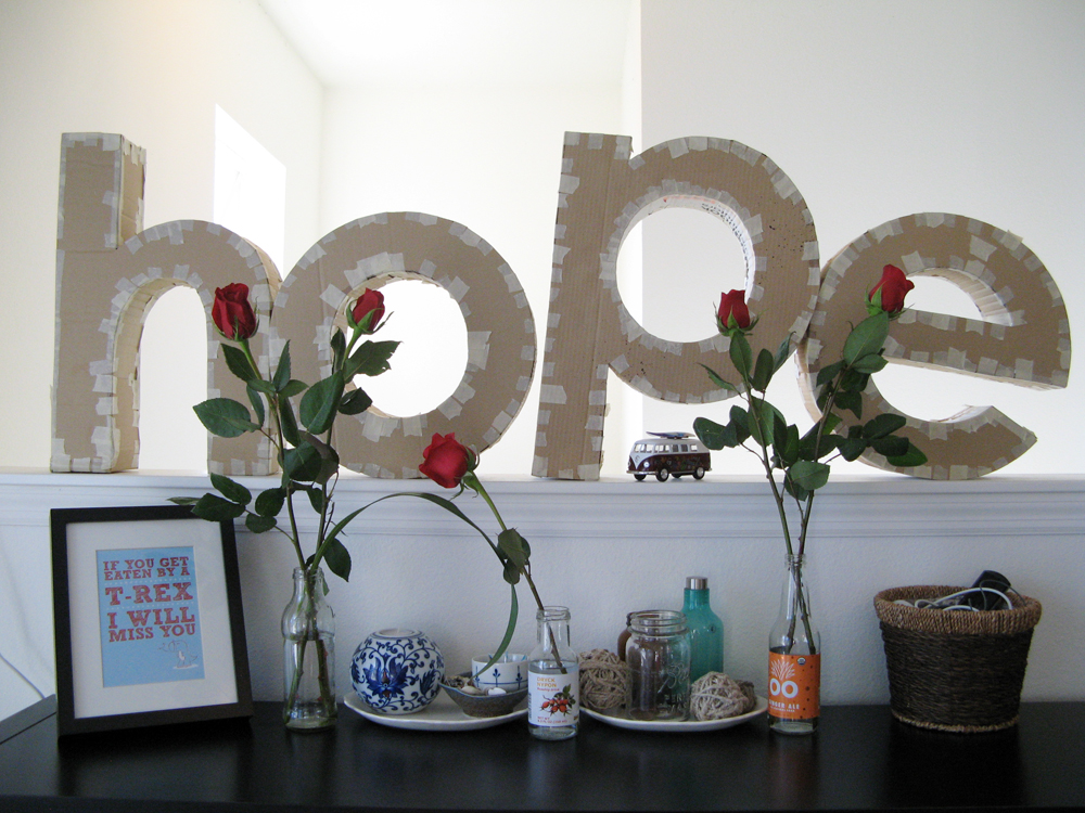 3d cardboard letters spelling out HOPE, roses in glass bottles, and t-rex print from Yellow Heart Art