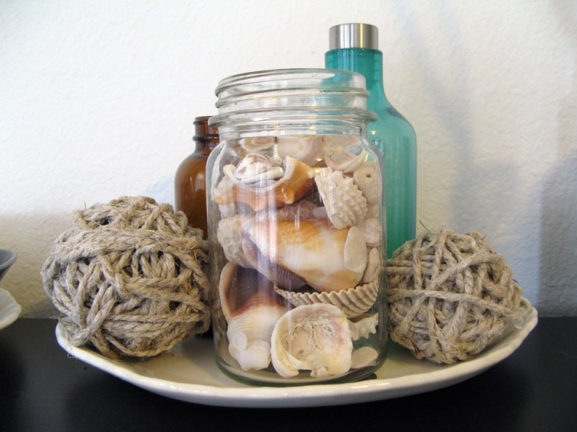 Seashells, brown and green bottles, twine, and an antique tray