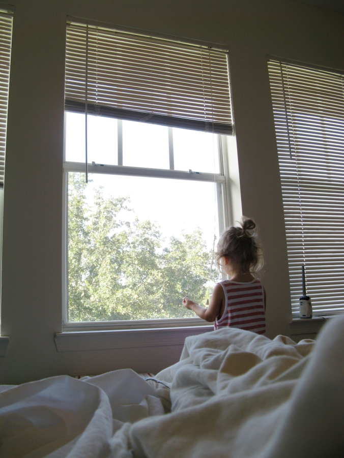 Tall windows in bedroom, messy bed, trees outside window