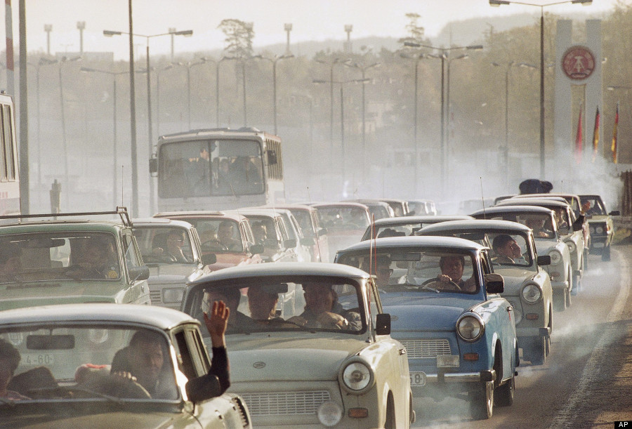 In a giant cloud of exhaust fumes of two-stroke engines, hundreds of East German cars wait bumper to bumper in front of the West German checkpoint Helmstedt to enter the west, Nov. 11, 1989. In front of the eastern checkpoint, the cars wait in line for a distance of 30-40 kilometers, a West German policeman said. The ride from Berlin to Helmstadt (about 200 kilometers) would last about 11 hours. (AP Photo/Claus Eckert)